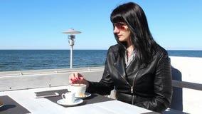 Ung kvinna som rör kaffe med en tesked i ett utomhus- kafé lager videofilmer
