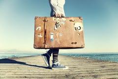 Ung kvinna som är klar att resa med hennes resväska Arkivfoto