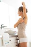 Ung kvinna som rakar armhålan i badrum royaltyfria foton