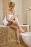 Ung kvinna som rakar henne ben arkivfoton