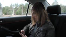 Ung kvinna som reser på baksätet av en bil stock video