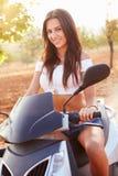 Ung kvinna som rider den motoriska sparkcykeln längs landsvägen Royaltyfria Foton