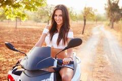 Ung kvinna som rider den motoriska sparkcykeln längs landsvägen Royaltyfria Bilder
