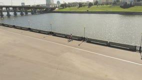 Ung kvinna som rider det fria för en cykel i sommar Flodinvallning Eco-v?nskapsmatch transport Flyg- skytte arkivfilmer