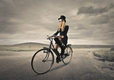 Ung kvinna som rider en cykel Fotografering för Bildbyråer