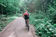 Ung kvinna som rider en cykel i parkera i rörelse, bakre sikt Fotografering för Bildbyråer