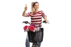 Ung kvinna som rider en cykel och gör en tumme upp tecken Royaltyfri Foto