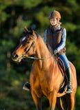 Ung kvinna som rider en häst. Fotografering för Bildbyråer