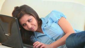 Ung kvinna som roar sig med hennes bärbar dator stock video