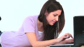 Ung kvinna som roar sig på hennes bärbar dator arkivfilmer