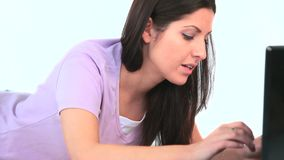 Ung kvinna som roar sig på hennes bärbar dator lager videofilmer