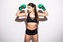 Ung kvinna som ropar och anfaller med gröna boxninghandskar som isoleras på vit arkivbild