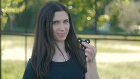 Ung kvinna som rotera en spinnare i hennes utomhus- hand Flickasnurrspinnare lager videofilmer