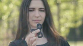 Ung kvinna som rotera en spinnare i hennes utomhus- hand Flickasnurrspinnare stock video