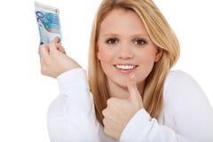 Ung kvinna som rymmer anmärkningen för euro 20 Royaltyfria Bilder
