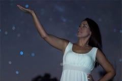 Ung kvinna som rymmer den defocused stjärnan Kvinna under stjärnklar natt Kvinna i den vita långa klänningen som ser till den stj Royaltyfria Foton