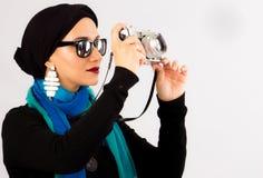 Ung kvinna som rymmer den gamla kameran i hijab och färgglad halsduk fotografering för bildbyråer