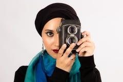 Ung kvinna som rymmer den gamla kameran i hijab och färgrik halsduk Arkivbild