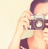 Ung kvinna som rymmer den gamla kameran Tappningeffekt Arkivfoton