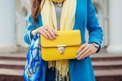 Ung kvinna som rymmer den stilfulla handväskan och bär det moderiktiga blåa laget Kläder och tillbehör för vår kvinnlig Mode fotografering för bildbyråer