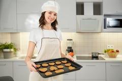 Ung kvinna som rymmer den svarta stekheta maträtten med smakliga kakor arkivfoton