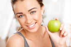 Ung kvinna som rymmer det gröna äpplet Royaltyfria Foton