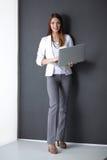 Ung kvinna som rymmer en bärbar dator som isoleras på grå färger Royaltyfri Bild
