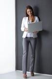 Ung kvinna som rymmer en bärbar dator som isoleras på grå färger Royaltyfria Foton