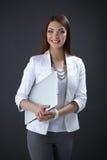 Ung kvinna som rymmer en bärbar dator som isoleras på grå färger Royaltyfria Bilder