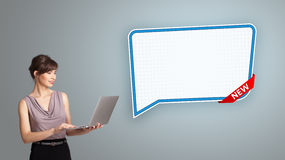 Ung kvinna som rymmer en bärbar dator och framlägger den moderna anförandebubblan Arkivbild