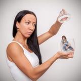 Ung kvinna som rymmer en glass krus, som sitter i lite flickan arkivbild