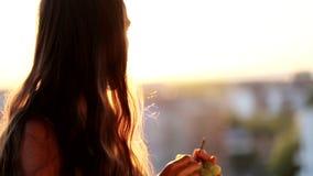 Ung kvinna som rymmer en grupp av druvan och äter dem på balkongen, närbild stock video