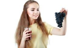 Ung kvinna som rymmer en grupp av druvor och ett exponeringsglas av fruktsaftisola Royaltyfria Bilder