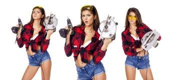 Ung kvinna som rymmer en konstruktionsdrillborr fotografering för bildbyråer