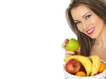 Ung kvinna som rymmer en korg av ny frukt royaltyfri bild