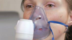 Ung kvinna som rymmer en maskering från en inhalator hemmastadd Behandlar inflammation av flygbolagen via nebulizeren Förhindra a lager videofilmer