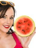 Ung kvinna som rymmer en ny mogen saftig vattenmelon Royaltyfri Foto