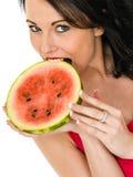 Ung kvinna som rymmer en ny mogen saftig vattenmelon Arkivbild