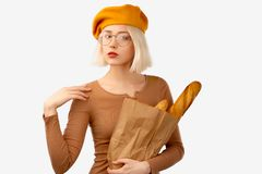 Ung kvinna som rymmer en påse med bagetten Den allvarliga kvinnliga handelsresanden håller armen på skuldran, den försäkrade blic arkivbilder