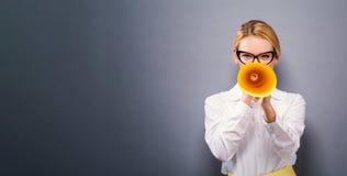 Ung kvinna som rymmer en pappers- megafon Royaltyfri Fotografi