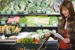 Ung kvinna som rymmer en shoppinglista arkivbild
