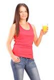 Ung kvinna som rymmer ett exponeringsglas av orange fruktsaft Royaltyfri Foto