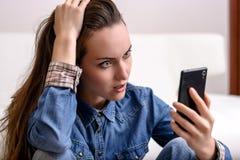 Ung kvinna som rymmer hans huvud och blickar till smartphonen Bedrövat av vad han såg royaltyfri fotografi