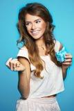 Ung kvinna som rymmer liten gåva slågen in i blått Royaltyfri Bild
