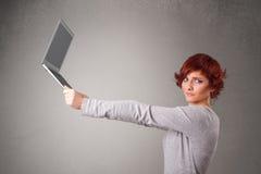 Ung kvinna som rymmer modern laptot Royaltyfri Foto