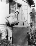Ung kvinna som sätter avskräde in i en soptunna (alla visade personer inte är längre uppehälle, och inget gods finns Leverantörbe Royaltyfria Foton