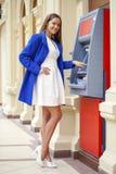 Ung kvinna som sätter in en kreditkort till ATM royaltyfri fotografi