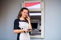 Ung kvinna som sätter in en kreditkort till ATM royaltyfri foto