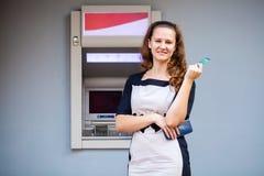Ung kvinna som sätter in en kreditkort till ATM fotografering för bildbyråer