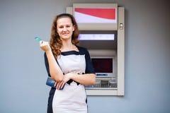 Ung kvinna som sätter in en kreditkort till ATM royaltyfri bild